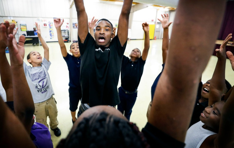 <strong>New Ballet Ensemble and School dancer instructor LeAnthony Douglas (middle) helps students at Dunbar Elementary School stretch before their hip-hop dance class Monday, Sept. 9. Douglas</strong><span><strong>&nbsp;was in New Ballet's first cohort at Dunbar Elementary as a third-grader and has been in his current role at New Ballet since graduating from Melrose High School in 2017.</strong>&nbsp;</span>(Mark Weber/Daily Memphian)