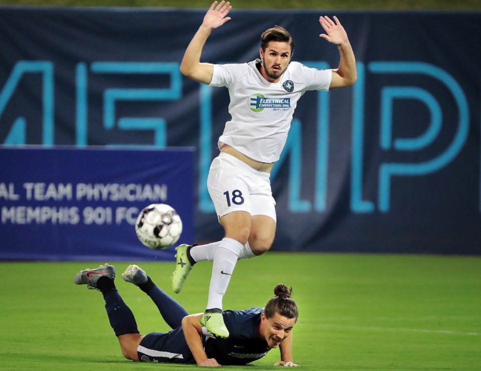 <strong>The St. Louis FC squad's Caleb Calvert (18) hurdles Memphis defender Marc Burch on a steal in the first half during 901FC's 1-0 win over St. Louis at AutoZone Park on Sept. 21, 2019.</strong> (Jim Weber/Daily Memphian)