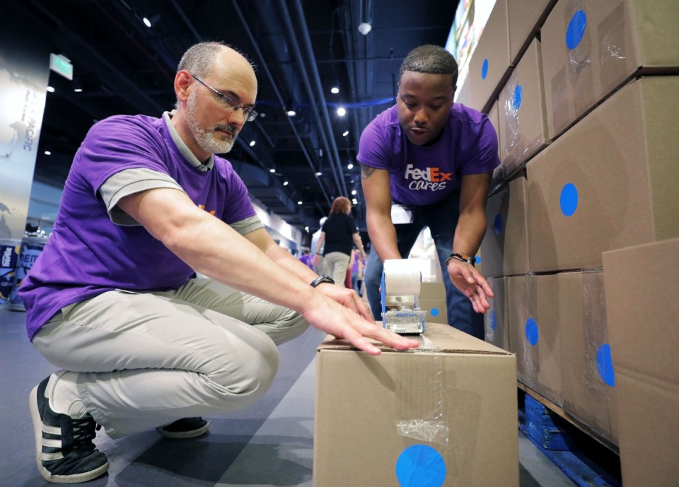 <strong>Cecell Hite (right) and Chad Dickson are among more than 200&nbsp;FedEx volunteers packing boxes Thursday at FedExForum. More than 12,000 care packages&nbsp; will be shipped to U.S. military personnel serving abroad.</strong> (Patrick Lantrip/Daily Memphian)