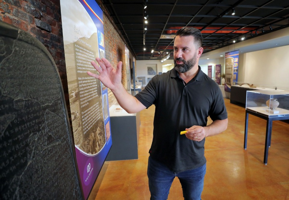 <strong>Craig Gyergyo, executive director of Bible Museum on the Square in Collierville, shows off a replica of the Moabite Stone Sept. 25, 2019, a tablet that dates back to the 8th century B.C.E. and is currently housed in the Louvre in France.</strong> (Patrick Lantrip/Daily Memphian)