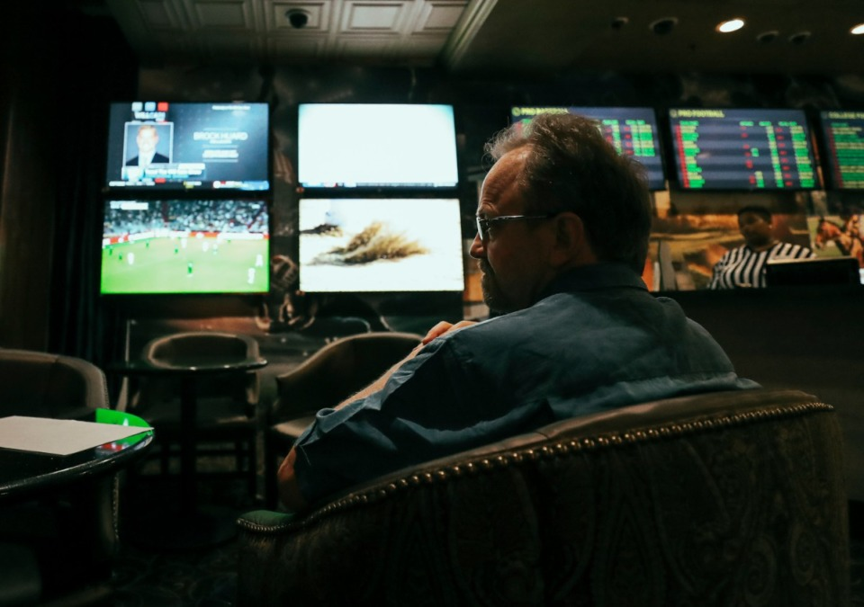<strong>A guest of Horeshoe Casino watches television screens in September, 2018, as he places bets on football at the casino's sport betting lounge.</strong> (Houston Cofield/Daily Memphian)