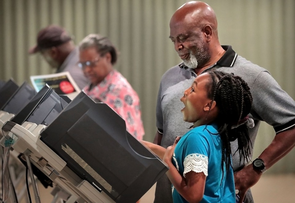 <strong>Olamide Tom, 8, reacts as Emmanuel Tom lets her push the button to register his vote on the last day of early voting at Abundant Grace Fellowship Church on Saturday, Sept. 28. Election day is Thursday, Oct. 3.</strong> (Jim Weber/Daily Memphian)