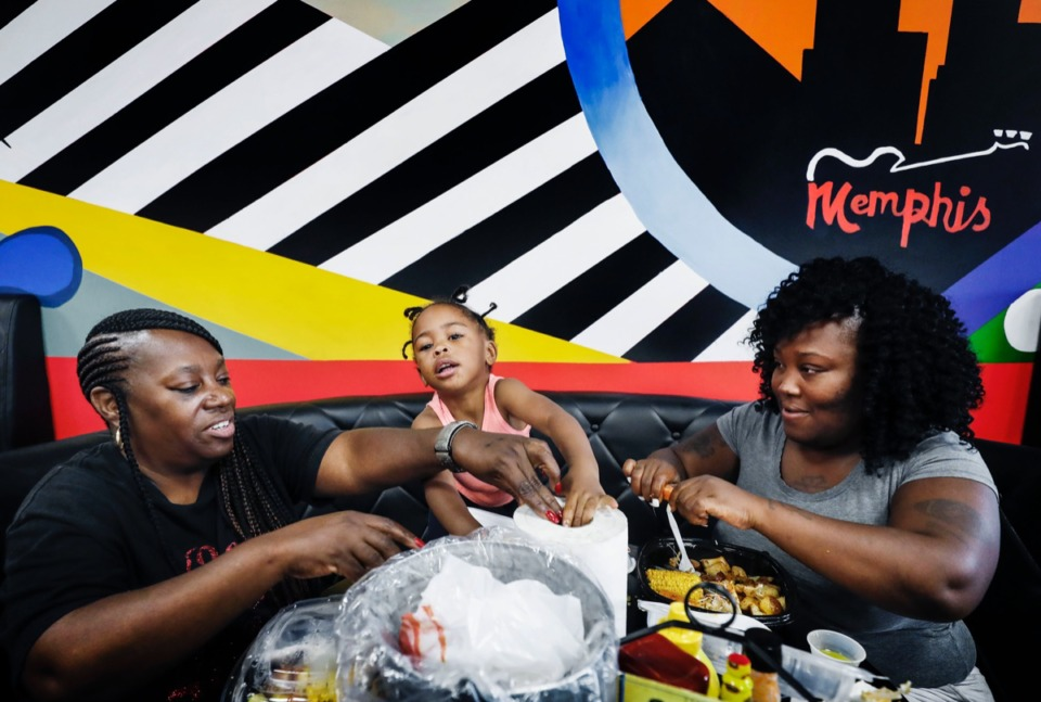<strong>DeeO's Seafood customers Nancy Hester (left) along with her granddaughter C'Myah Jones (middle) and daughter Erica Hester (right) enjoy a seafood boil for on Tuesday, Oct. 1, 2019.</strong> (Mark Weber/Daily Memphian)
