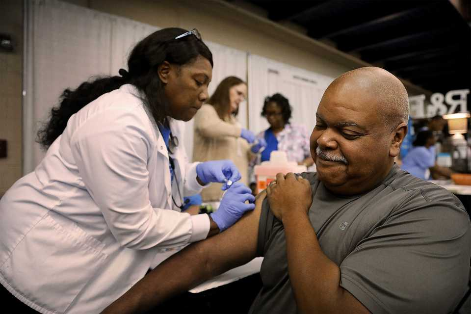 <strong>Regina Morris gives Johnny Jones a free flu shot at Baptist Memorial Hospital's booth during the annual Collierville Business Expo on Oct. 25, 2018. (Patrick Lantrip/Daily Memphian)&nbsp;</strong>