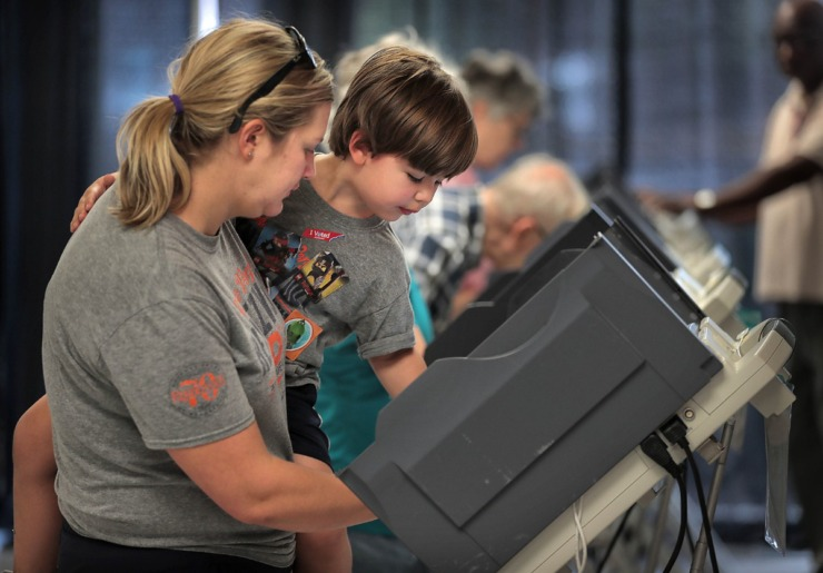 <strong>Katherine Riederer (left) lets Will Riederer, 4, push the button to cast her final ballot at Mississippi Boulevard Christian Church. Memphians turned out to vote on a number of local elections on Oct. 3, 2019 including a sales tax increase, City Council races and a contentious mayoral race.</strong> (Jim Weber/Daily Memphian)