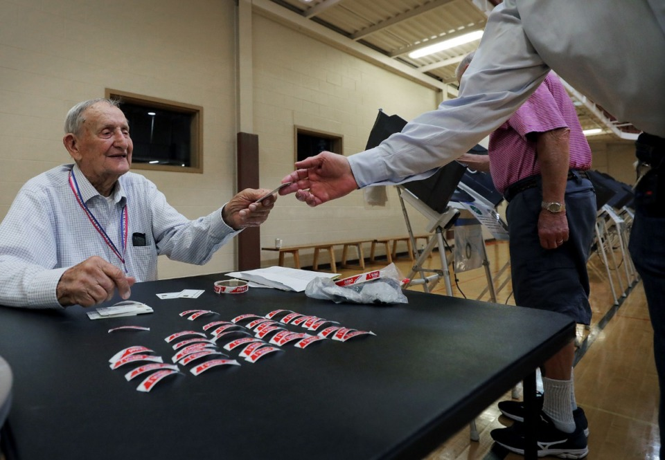 """<strong>An election worker passes out """"I voted"""" stickers to voters casting ballots at the Second Baptist Church polling location on Oct. 3, 2019.</strong> (Patrick Lantrip/Daily Memphian)"""