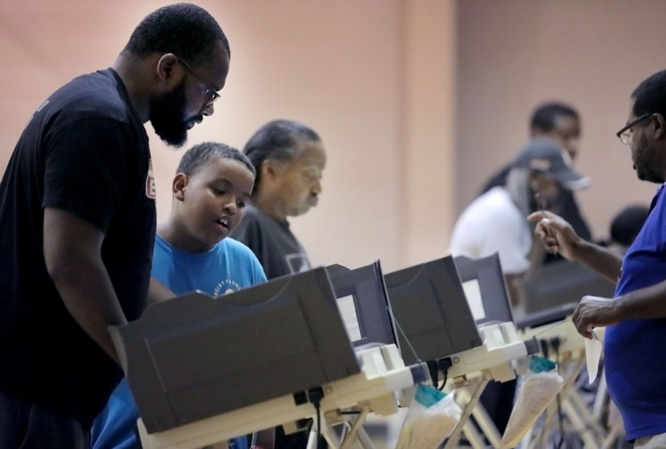 <strong>Mustafa Shaw watches his father Malik Shaw (far left) casts his vote at the Dave Wells Community Center gymnasium polling location Oct. 3.</strong> (Patrick Lantrip/Daily Memphian)