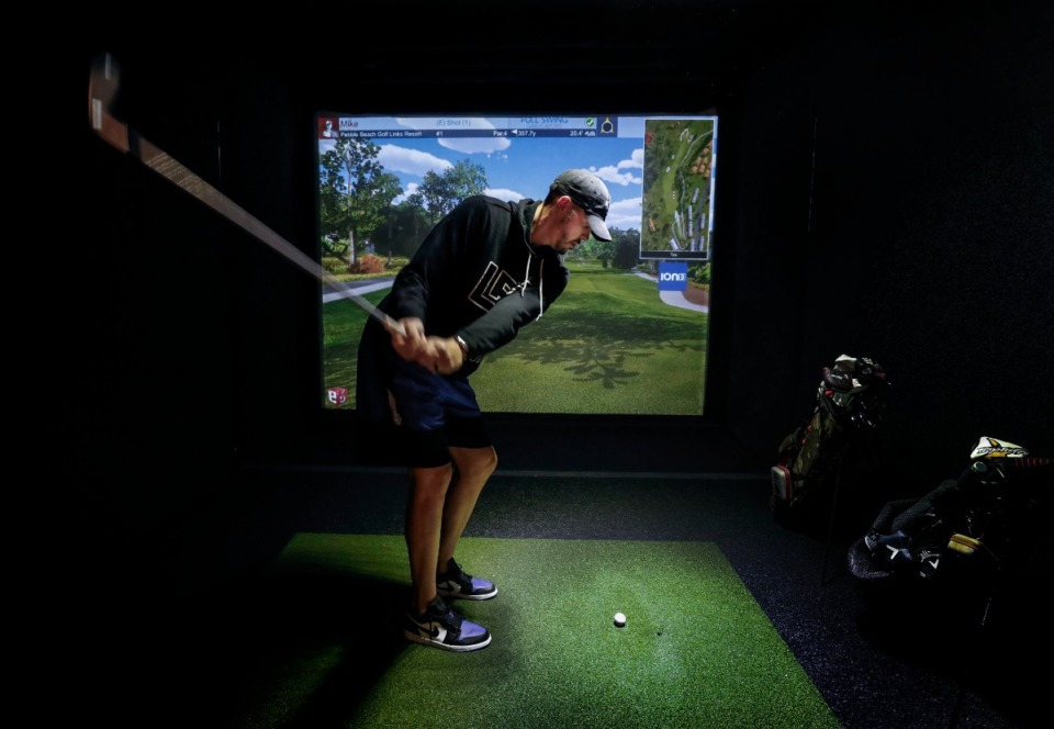 <strong>Mike Miller takes some swings on a golf simulator at his new restaurant in Germantown on Sept. 23, 2019. Let It Fly will allow customers to play golf on two simulators while indulging in a full range of bar snacks.</strong> (Mark Weber/Daily Memphian)