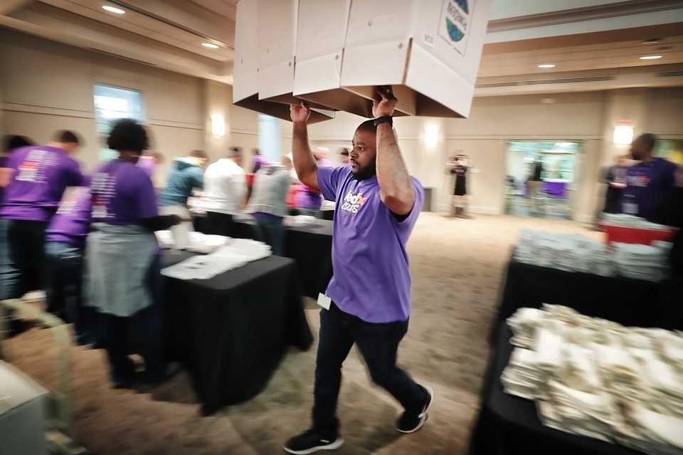 """<p class=""""p1""""><span class=""""s1""""><b>FedEx volunteer Shannon Bell delivers boxes to be filled with hygiene kits at the Memphis Botanic Garden. </b>(Jim Weber/Daily Memphian)</span>"""