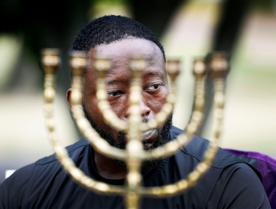"<strong>Meekos Evans, seen through a menorah, learns about the Jewish faith during the ""Ask Me Anything"" event at Health Sciences Park on Oct. 5, 2019. Community members ask questions they may have to faith leaders to help create a mutual understanding and respect for their communities.</strong> (Mark Weber/Daily Memphian)"