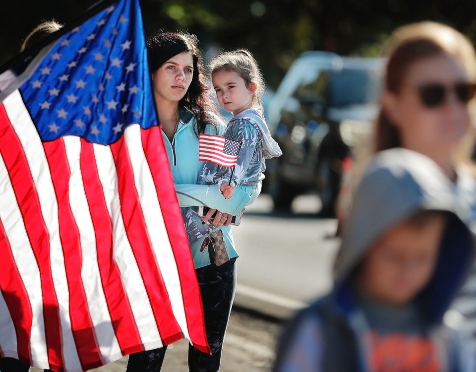 <strong>Hassen Hawkins (left) and Tatum Brahm, 4, join a crowd of Germantown residents lining the street along Winchester to honor Major Trevor Joseph.</strong> (Jim Weber/Daily Memphian)