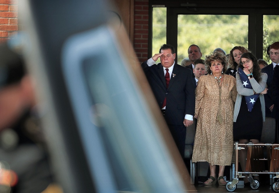 <strong>Erin Joseph (right), wife of Major Trevor Joseph, clutches the flag she was given as she stands with the soldier's parents, Nancy Joseph and Pete Joseph (center), watching the casket being taken away during a memorial service for the Houston High grad and medevac pilot on Oct. 8.</strong> (Jim Weber/Daily Memphian)
