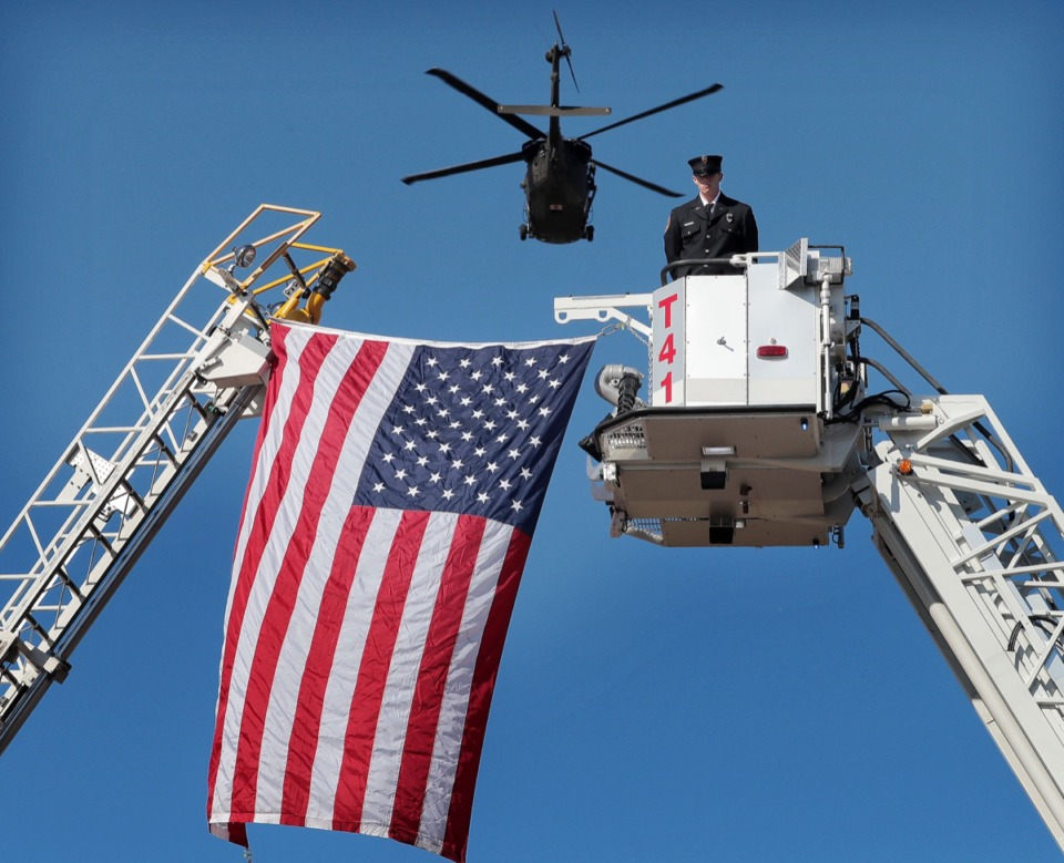 <strong>A Black Hawk helicopter flies low over an arch made from Germantown Fire Department ladder trucks set up on Winchester as firefighter Cody Hughes stands at attention to honor a funeral procession for Major Trevor Joseph, a Houston High grad and Medevac pilot, on Oct. 8, 2019. The Mid-South soldier was killed in a helicopter crash last month in Louisiana.</strong> (Jim Weber/Daily Memphian)