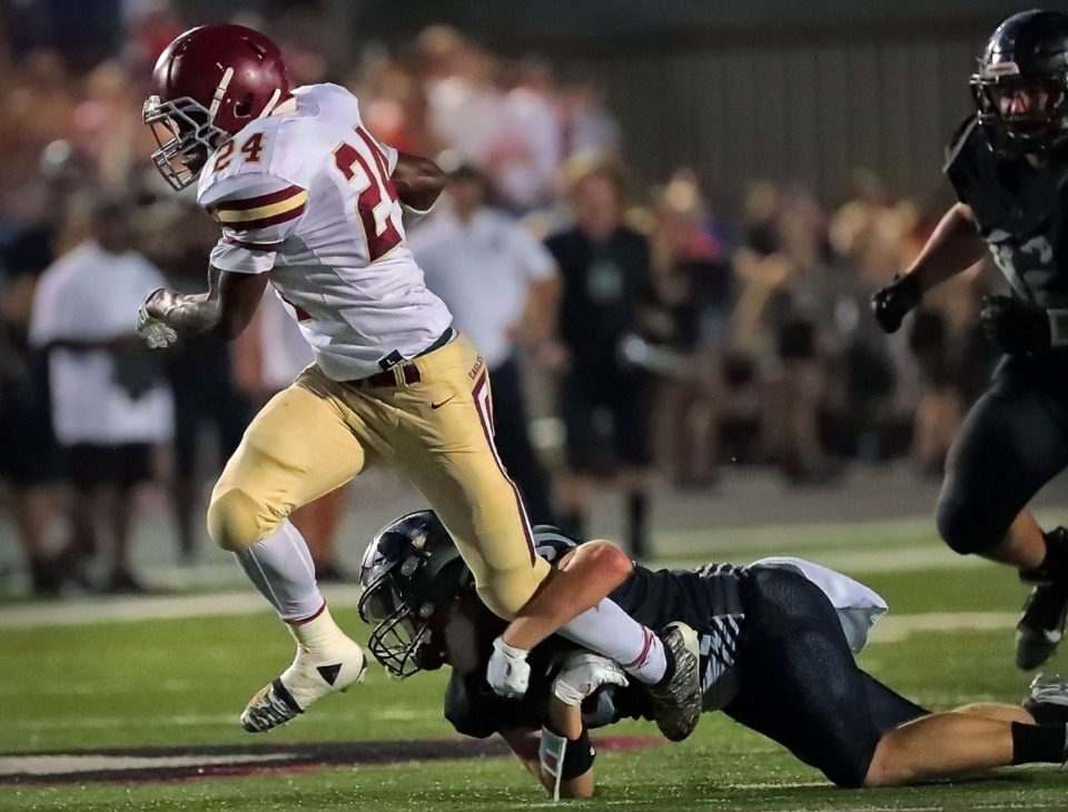 <strong>Evangelical Christian School running back Jaylen Greenwood (24) tries to shake loose a defender during Houston High School's 36-20 win Sept. 13 over ECS.</strong> (Jim Weber/Daily Memphian)