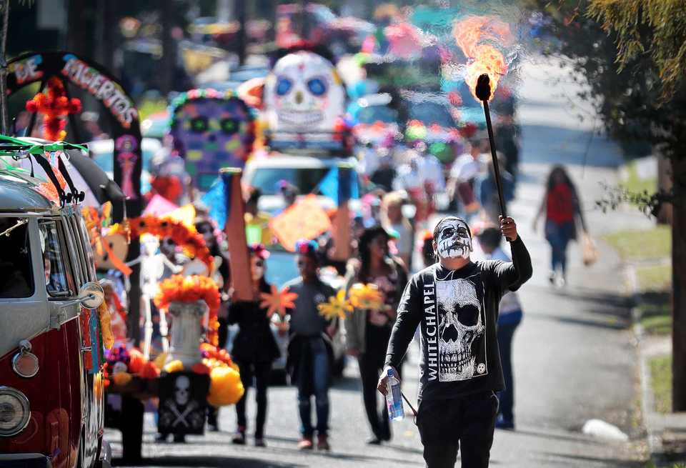 <strong>Carlos Valverde (right) escorts the Dia de los Muertos (Day of the Dead) parade from Overton Square to Overton Park on Oct. 27, 2018. The parade and fiesta are put on by the Brooks Museum of Art and Cazateatro Bilingual Theatre Group drawing from the Latin American tradition of honoring ancestors and celebrating the cycle of life and death.</strong> (Jim Weber/Daily Memphian)