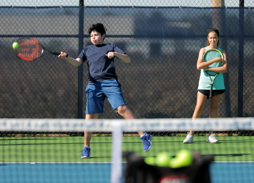 <strong>Oscar Rodriguez stretches for the ball while Emma Sheridan watches at the Arlington Sports Complex's new tennis courts on Oct. 8, 2019.</strong> (Patrick Lantrip/Daily Memphian)