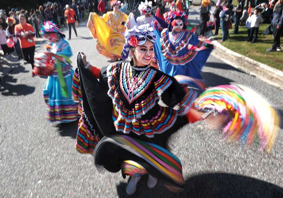 <strong>Jessica Mendoza and fellow dancers with Herencia Hispana enter Overton Park with a flourish during the a Dia de los Muertos (Day of the Dead) parade from Overton Square to Overton Park on Oct. 27, 2018. The parade and fiesta are put on by the Brooks Museum of Art and Cazateatro Bilingual Theatre Group drawing from the Latin American tradition of honoring ancestors and celebrating the cycle of life and death.</strong> (Jim Weber/Daily Memphian)