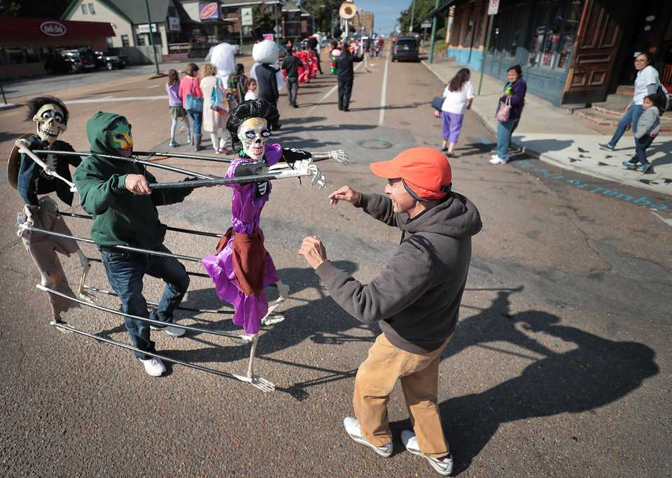 <strong>Angel Gonzalez (right) dances with Addofo Montiel and his skeleton puppets during the a Dia de los Muertos (Day of the Dead) parade from Overton Square to Overton Park on Oct. 27, 2018. The parade and fiesta are put on by the Brooks Museum of Art and Cazateatro Bilingual Theatre Group drawing from the Latin American tradition of honoring ancestors and celebrating the cycle of life and death.</strong> (Jim Weber/Daily Memphian)