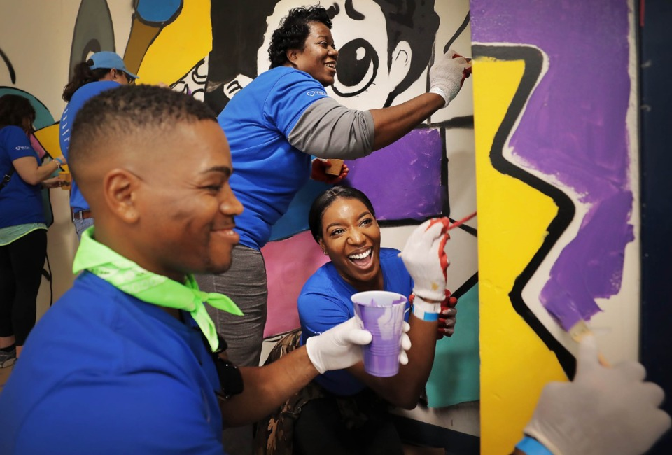 <strong>ServiceMaster analysts Corey Lewis (left) Natoya Matthews and Kelly Booker-Miller (top) help paint a mural Thursday at Bruce Elementary&nbsp; for national We Care Day. Servicemaster volunteers partnered with 17 local groups to complete 26 projects in the Memphis area.</strong> (Jim Weber/Daily Memphian)