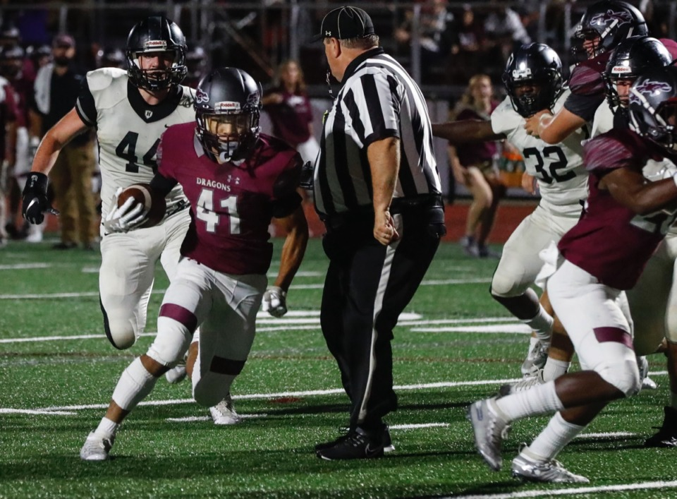 <strong>Collierville running back Duple Travillion (left) runs past an official with the Houston defense in hot pursuit Oct. 10.</strong> (Mark Weber/Daily Memphian)