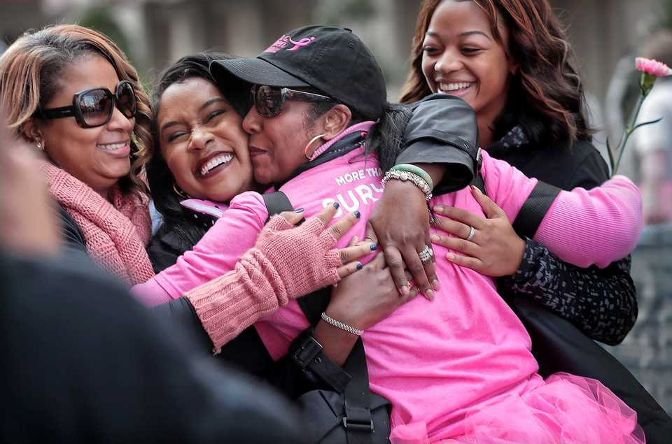 <strong>Gloria Boyce, center, is embraced by Angela Thomas, left, Davielle Hotz, and Andriona Thomas (right) at the finish line after completing the Susan G. Komen Race for the Cure on Oct. 27, 2018. Downtown Memphis was flooded with pink tutus, pink wigs and pink feathered boas Saturday morning as over 6,000 runners turned out for the annual race to raise money to fund research, education, screening and treatment of breast cancer.</strong> (Jim Weber/Daily Memphian)