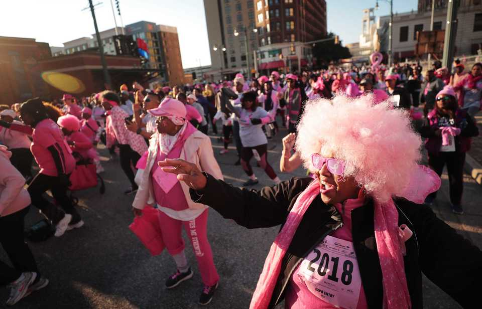 <strong>Josephine Vaughn (right) gets warmed up with a little dancing before the start of the Susan G. Komen Race for the Cure on Oct. 27, 2018. Downtown was flooded with pink tutus, pink wigs and pink feathered boas Saturday morning as over 6,000 runners turned out for the annual race to raise money to fund research, education, screening and treatment of breast cancer.</strong> (Jim Weber/Daily Memphian)