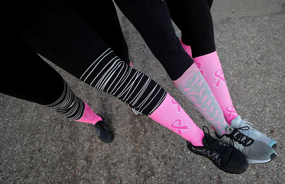 <strong>Julie Brown (left), Sonya Bradford and Tonia Thomas compare socks at the finish line after the Susan G. Komen Race for the Cure on Oct. 27, 2018. Downtown was flooded with pink tutus, pink wigs and pink feathered boas Saturday morning as over 6,000 runners turned out for the annual race to raise money to fund research, education, screening and treatment of breast cancer.</strong> (Jim Weber/Daily Memphian)