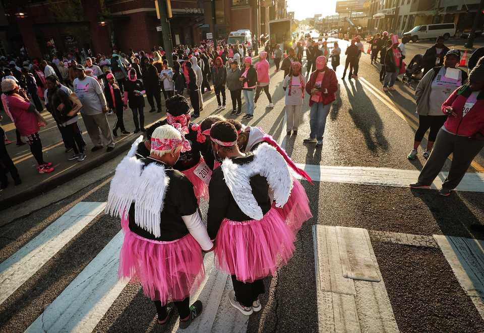 <strong>Members of the Nurses, Angels, and Warriors Team pray before the start of the Susan G. Komen Race for the Cure on Oct. 27, 2018. Downtown was flooded with pink tutus, pink wigs, and pink feathered boas Saturday morning as over 6,000 runners turned out for the annual race to raise money to fund research, education, screening and treatment of breast cancer.</strong> (Jim Weber/Daily Memphian)