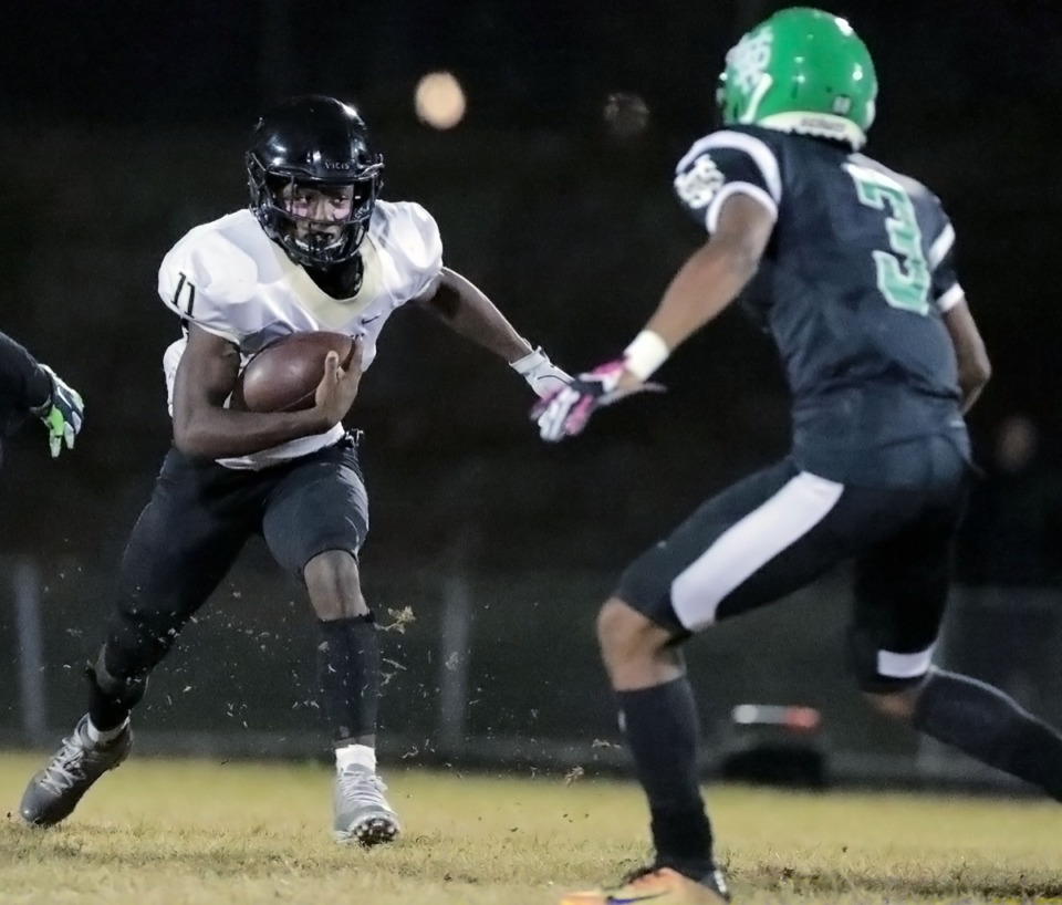 <strong>Whitehaven High School running back Cameron Sneed (11) charges a White Station defender miss during the game Oct. 11 at the Mid-South Fairgrounds.</strong> (Patrick Lantrip/Daily Memphian)
