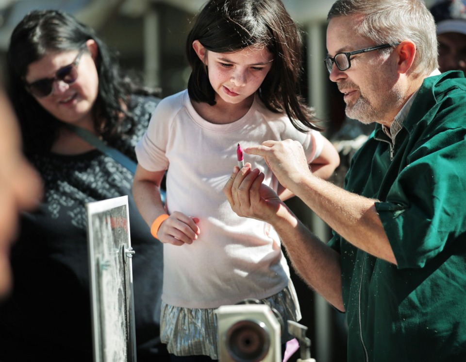 <strong>Arianna Allen, 8, learns how to color a top from Jack Waggoner (right) with the Midsouth Woodturners Guild using a wood lathe during the 47th annual Pink Palace Crafts Fair on Oct. 12, 2019 at Audubon Park. The event features some 200 craftsman peddling a range of handmade goods including pottery, textiles, glass, jewelry and fine art to raise money for the Pink Palace family of museums.</strong> (Jim Weber/Daily Memphian)