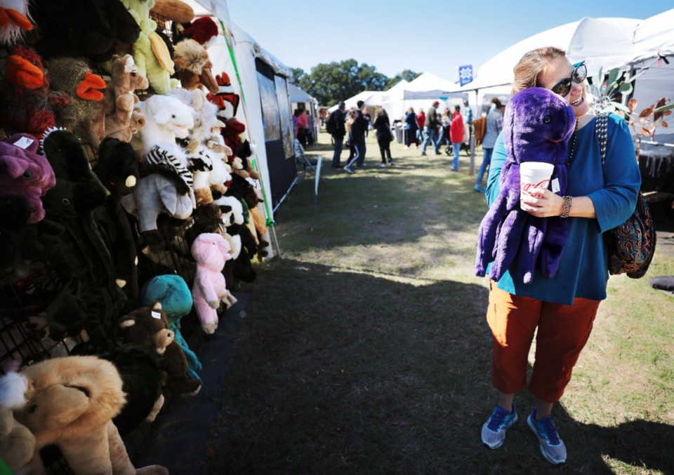 <strong>Jane Ruffin gets attached to a purple octopus puppet at the Lucy's Toys booth during the 47th annual Pink Palace Crafts Fair on Oct. 12, 2019 at Audubon Park. The event features some 200 craftsman peddling a range of handmade goods including pottery, textiles, glass, jewelry and fine art to raise money for the Pink Palace family of museums.</strong> (Jim Weber/Daily Memphian)