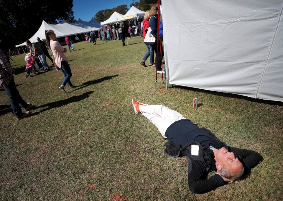 <strong>Kathe Williams takes a break from helping out at the Katie Dann Artwear booth during the 47th annual Pink Palace Crafts Fair on Oct. 12, 2019 at Audubon Park. The event features some 200 craftsman peddling a range of handmade goods including pottery, textiles, glass, jewelry and fine art to raise money for the Pink Palace family of museums.</strong> (Jim Weber/Daily Memphian)