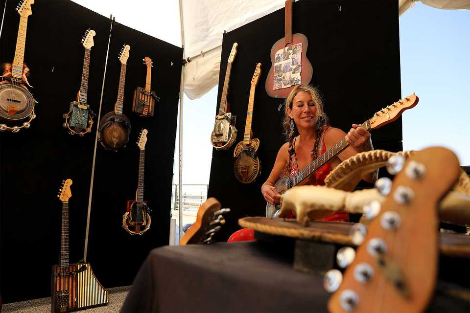 <strong>Lydia Randolph takes some time off from selling paintings in her adjacent booth to play a song on one of her friend&rsquo;s guitars. </strong>(Patrick Lantrip/Daily Memphian)