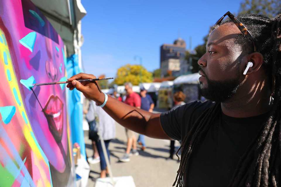 <strong>Jamond Bullock works on a painting at one of the hands-on artist demonstrations held on Sunday, Oct. 28, at the RiverArtsFest, a two-day artist market and urban street market.</strong> (Patrick Lantrip/Daily Memphian)