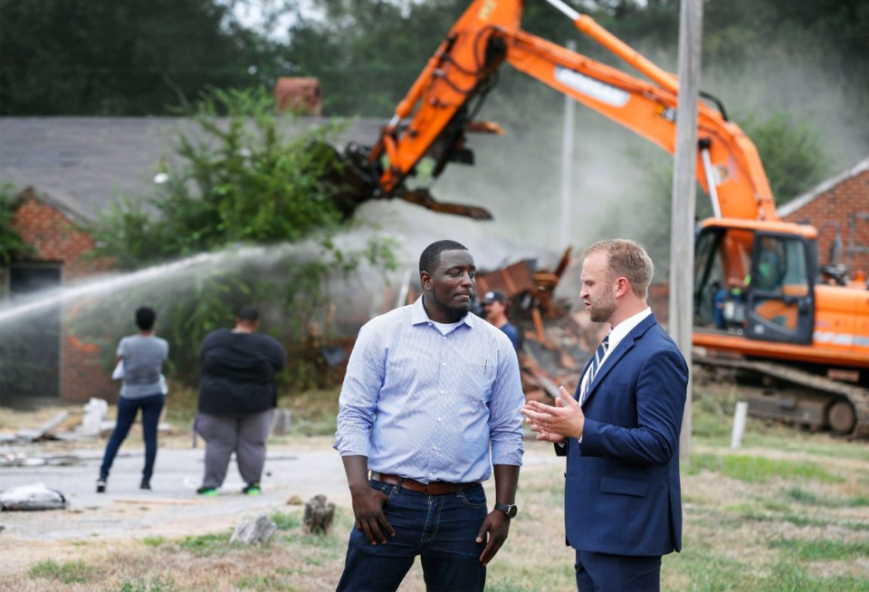 <strong>General Contractor Octavius Nickson (left) and Noah Gray, executive director of the Binghampton Development Corp., chat as a bulldozer razes vacant homes on Tillman Cove. during 'Demolition Day' ceremony Sept. 9.</strong> (Mark Weber/Daily Memphian file)