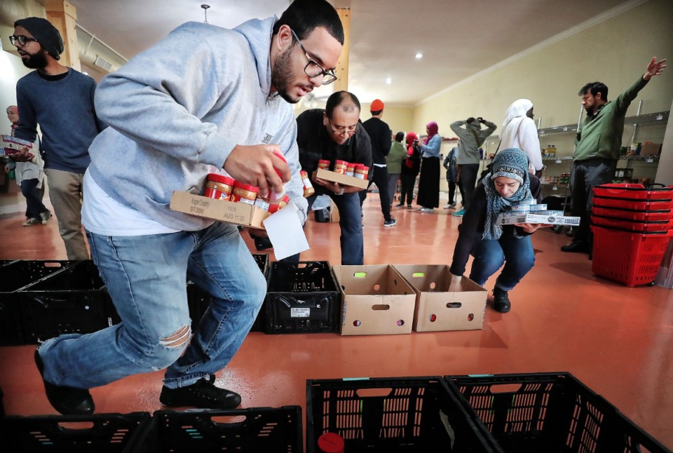 <strong>Bilal Simmons sorts through peanut butter and other non-perishables as volunteers gather on Oct. 12 at the Midtown Mosque to package Halal food for people in need around the neighborhood.</strong> (Jim Weber/Daily Memphian)