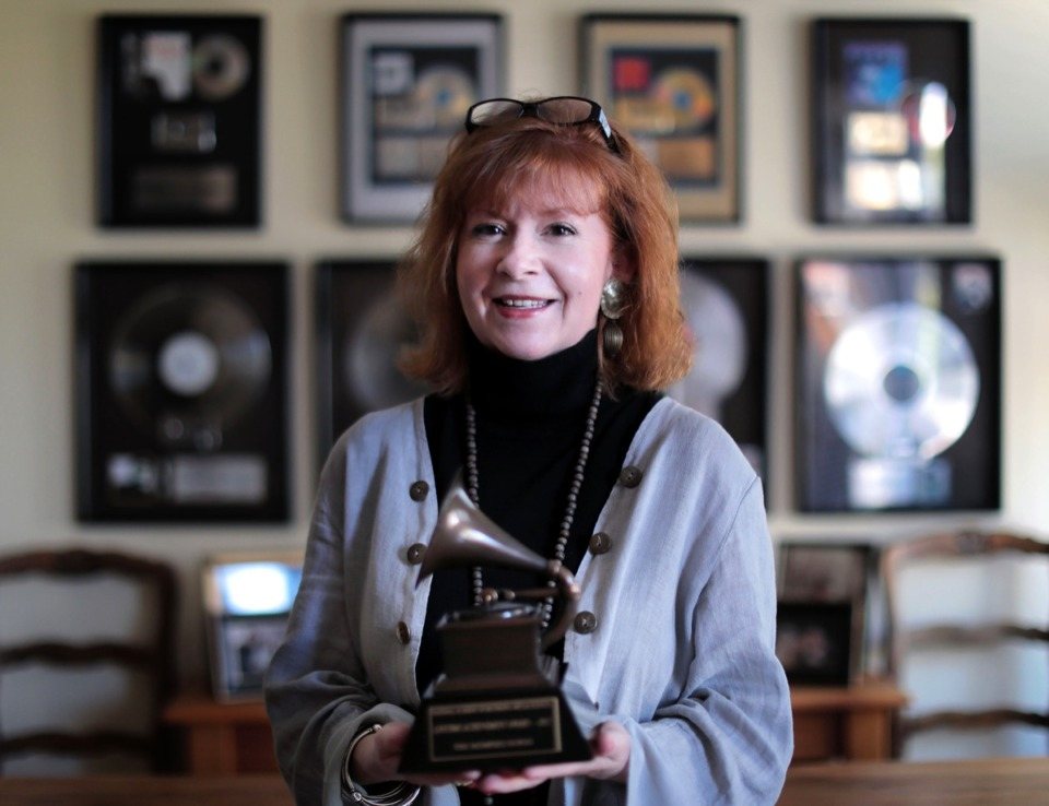 <strong>Amy Jackson, wife of the late Wayne Jackson, stands in front of just a few of her husband's platinum records on display in her Harbor Town living room while holding his Grammy Lifetime Achievement Award Oct. 9.</strong> (Patrick Lantrip/Daily Memphian)