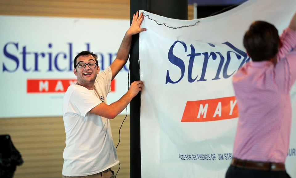 <strong>Daniel Saharovich (left) and volunteer Cole Perry help set up Jim Strickland's campaign headquarters on July 30, 2019, in the Poplar Plaza shopping center.</strong> (Jim Weber/Daily Memphian file)