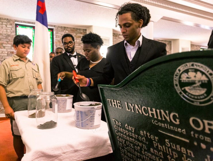 "<strong>During the Lynching Site Project memorial at Collins CME Chapel Church in&nbsp;<span class=""s1"">Downtown Memphis on Oct. 19, 2019</span>, LeMoyne-Owen Choir members Emmanuel Lugo (from right), Dorneisha Bowling and Jon Turner place portions of earth in jars to represent paying respects at the burials of two Memphis lynching victims.</strong>&nbsp;<span class=""s1"">(Ziggy Mack/Special to The Daily Memphian)</span>"