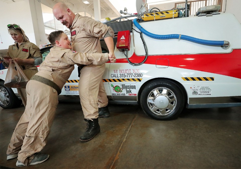 """<strong>""""Ghostbusters"""" fanboy Cory Coffman (right) roughhouses with his son Aiden Coffman, 9, during the annual Memphis Comic Expo at the Agricenter on Oct. 19, 2019. The two-day show features artists, a cosplay contest, a video game tournament and a slew of comic vendors.</strong> (Jim Weber/Daily Memphian)"""