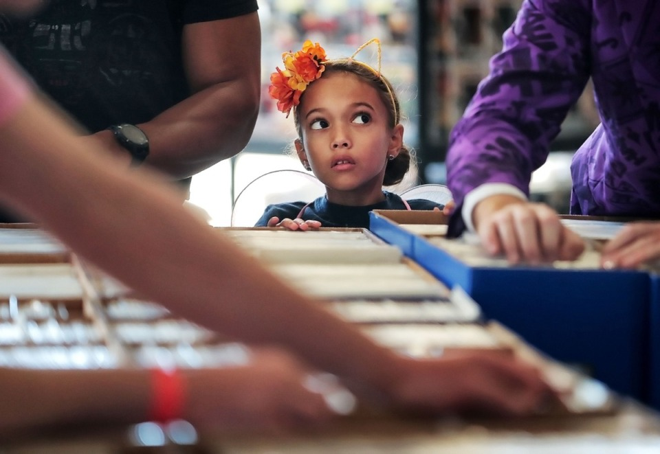<strong>Layla Tanzillo, 7, keeps an eye on fellow comic hunters while her dad looks for a DC Supergirl issue during the annual Memphis Comic Expo at the Agricenter on Oct. 19, 2019. The two-day show features artists, a cosplay contest, a video game tournament and a slew of comic vendors.</strong> (Jim Weber/Daily Memphian)