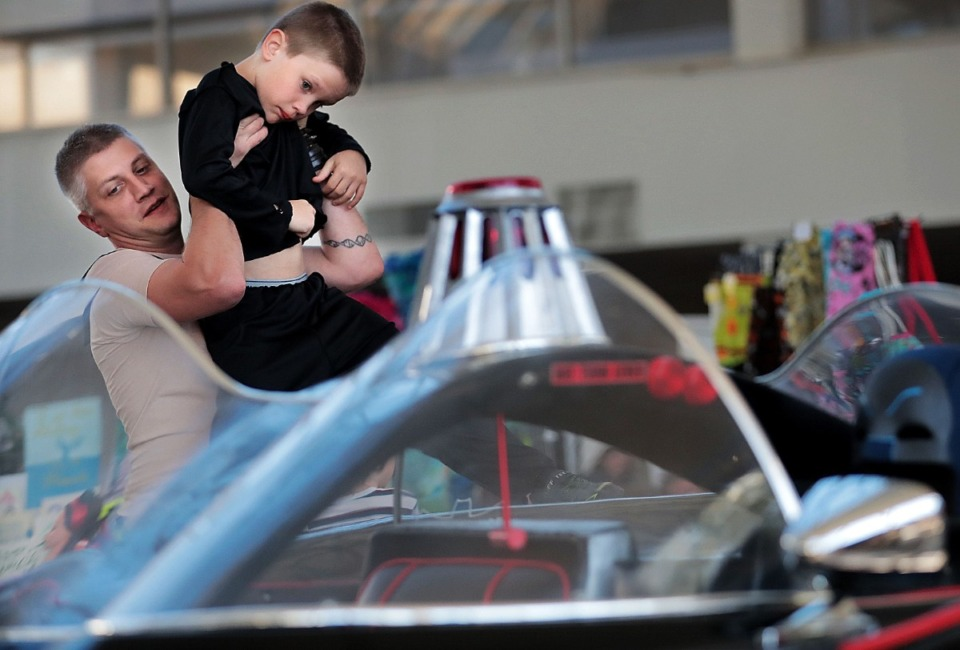 <strong>Bobby Green (left) gives his son Ian, 9, a boost to get a better look at the vintage batmobile on display during the annual Memphis Comic Expo at the Agricenter on Oct. 19, 2019. The two-day show features artists, a cosplay contest, a video game tournament and a slew of comic vendors.</strong> (Jim Weber/Daily Memphian)