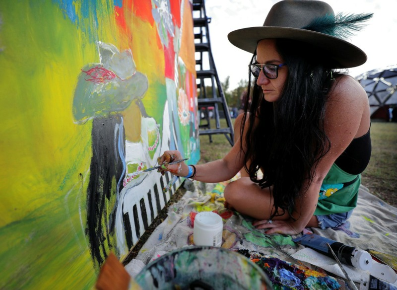<strong>Kristen Allen, a painter hired by the Mempho Music Fest, works on her piece while singing along to Margo Price's performance during the music festival at Shelby Farms on Oct. 19, 2019.</strong> (Patrick Lantrip/Daily Memphian)