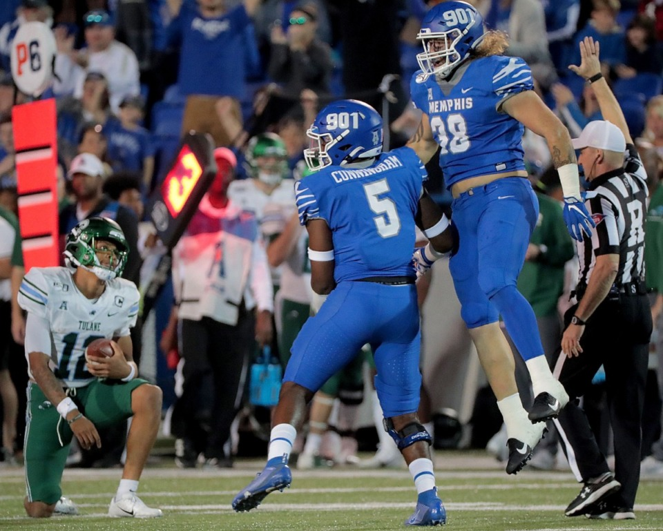 <strong>University of Memphis defenders Everitt Cunningham (5) and Jonathan Wilson (38) celebrate after taking down Tulane&nbsp; quarterback Justin McMillan for a loss of yards during the Tigers game on Oct. 19, 2019, against the Green Wave at Liberty Bowl Memorial Stadium in Memphis.</strong> (Jim Weber/Daily Memphian)