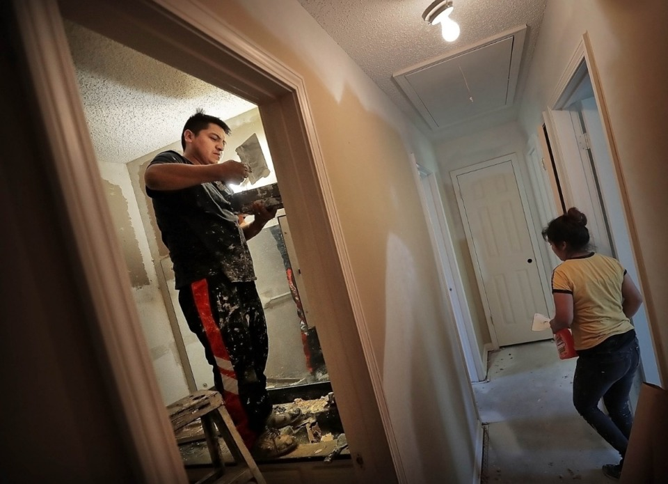<strong>Santos (left) and Sofia Vasquez with Bross Construction repair drywall while renovating a home in Southeast Memphis for resale.</strong> (Jim Weber/Daily Memphian)