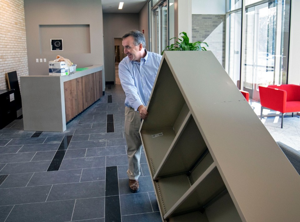 <strong>Germantown Municipal School District Superintendent Jason Manuel wheels a dolly carrying a shelf through the lobby of a building on the Forest Hill Elementary property where administrators and staff will work.&nbsp;</strong> (Mike Kerr/Special to Daily Memphian)