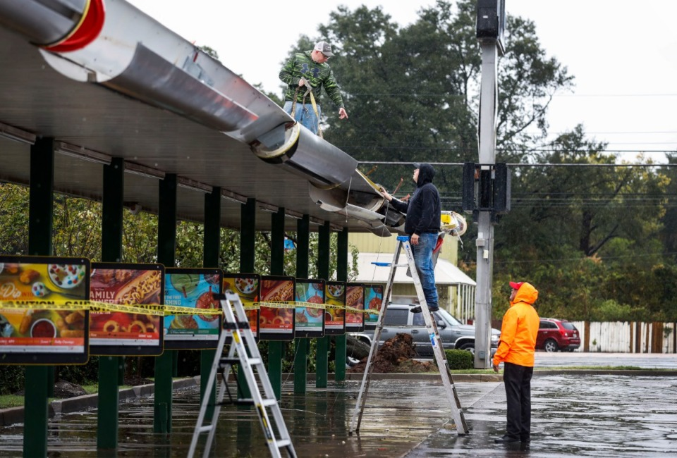 <strong>Workers clear storm damage at the Sonic on Perkins Avenue after heavy rains and high winds hit the Parkway Village area early Monday, Oct. 21, 2019.</strong> (Mark Weber/Daily Memphian)