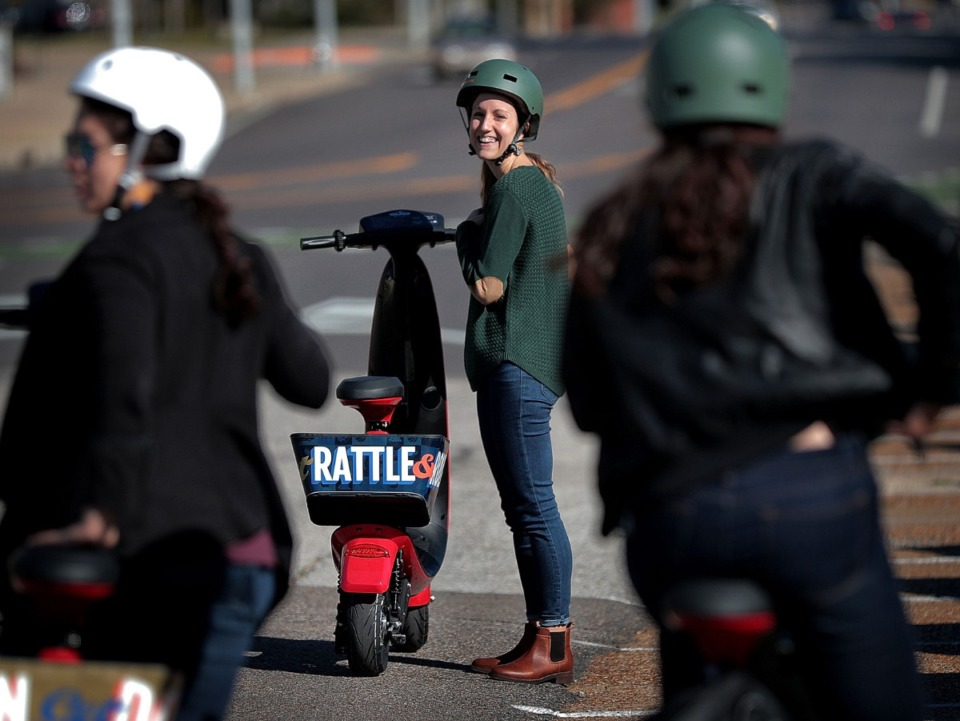<strong>Becca Hand (center) waits for her friends to gear up for a ride during the roll out of new OjO scooters by Explore Bike Share on Wednesday, Oct. 23, near Crosstown. OjOs are seated electric scooters that will share docking stations with the Explore bikes.</strong> (Jim Weber/Daily Memphian)