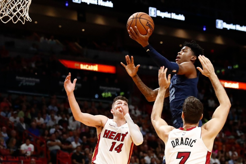 <strong>Memphis Grizzlies guard Ja Morant (12) shoots the ball against Miami Heat guards Tyler Herro (14) and Goran Dragic (7) during the first half of an NBA basketball game Wednesday, Oct. 23, in Miami.</strong> (Brynn Anderson/AP)