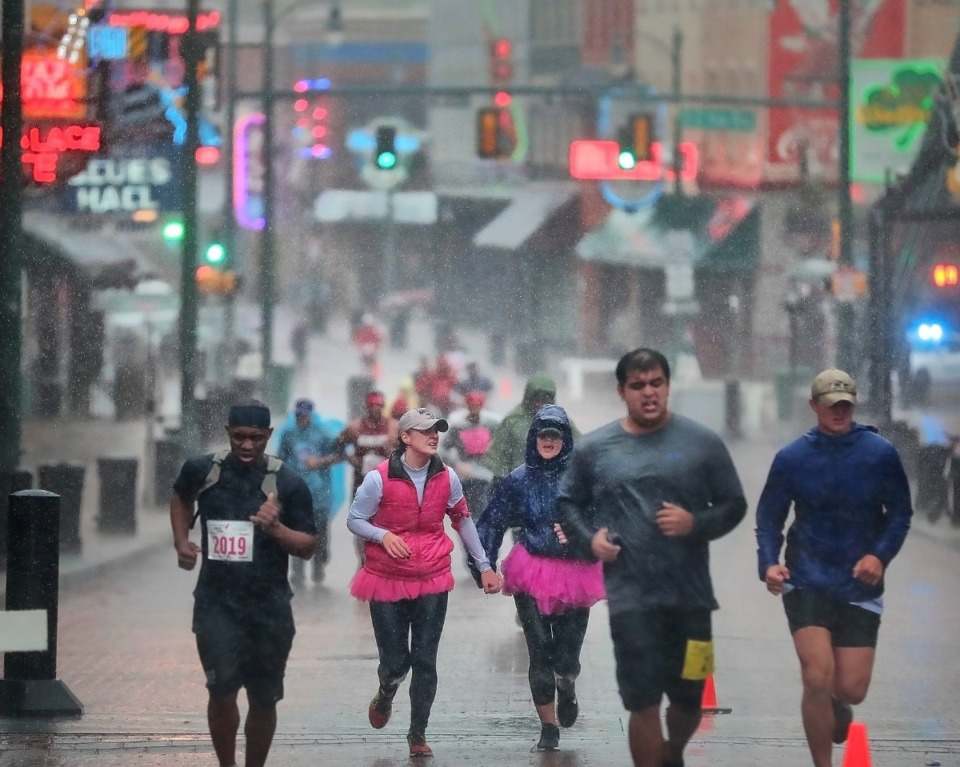 <strong>Runners slog through the heavy rain on Beale Street to raise money to fund breast cancer research, education, screening and treatment.</strong> (Jim Weber/Daily Memphian)
